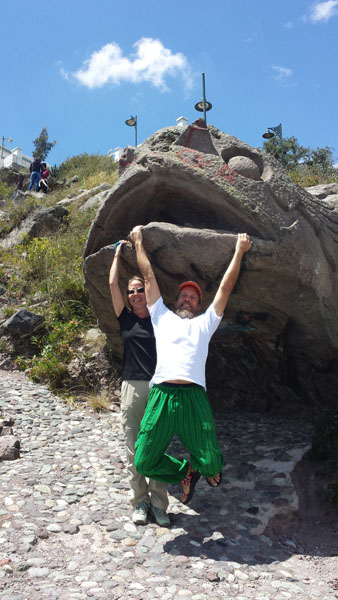 Raft guide hanging from a stone mouth near Guano Ecuador