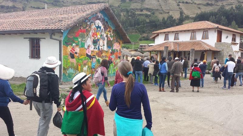 Visiting La Moya Comunitario. Note the church mural in the background.