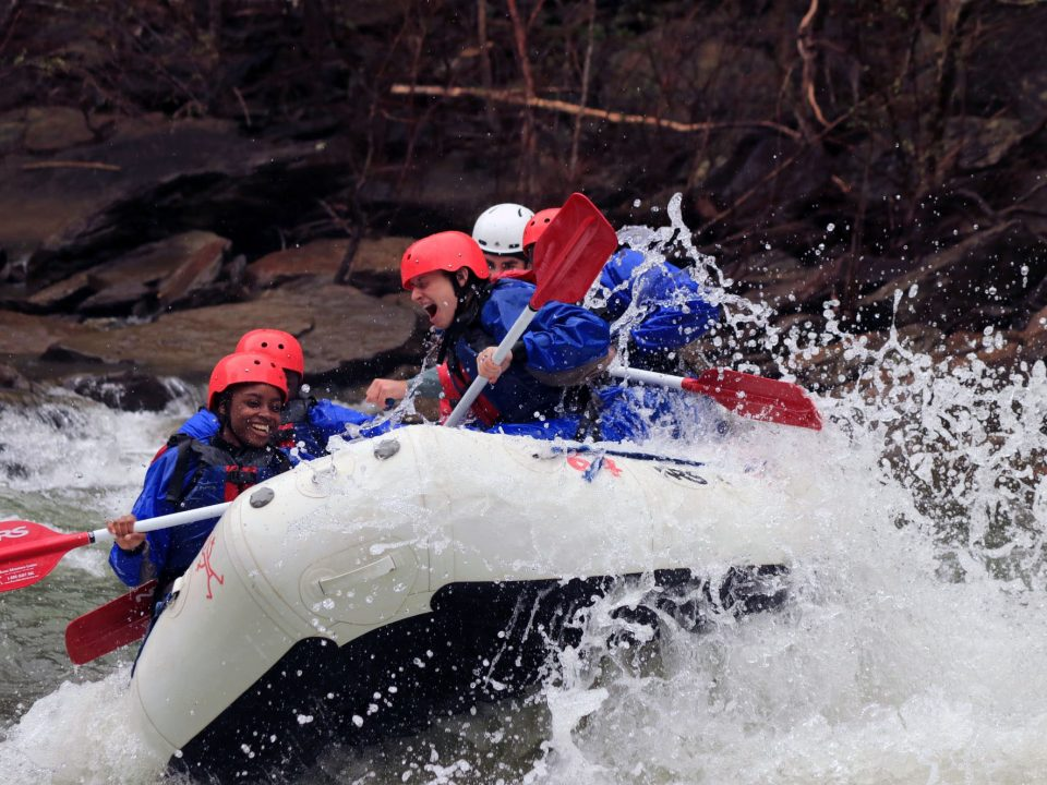 Rafters wearing splash gear in a white raft at double trouble on the Ocoee River